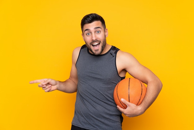 Handsome young basketball player man over isolated white wall surprised and pointing side