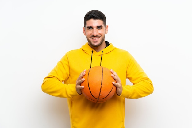 Handsome young basketball player man over isolated white wall