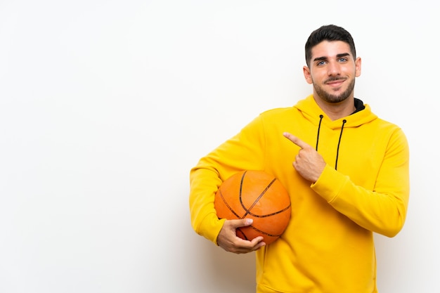 Handsome young basketball player man  on white wall pointing to the side to present a product