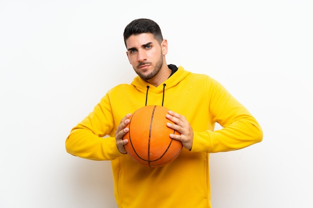 Handsome young basketball player man  on white wall