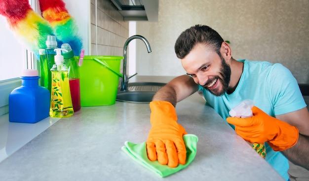 Tシャツを着たハンサムな若いあごひげの男が家の掃除中にキッチンで特別なツールでテーブルを拭いています