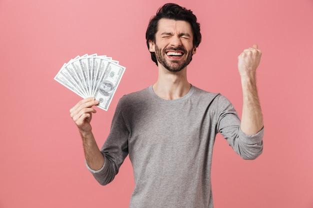 Красивый молодой бородатый брюнет в свитере стоит над розовым, показывая денежные купюры
