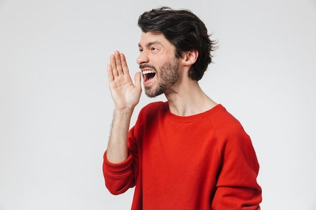 白の上に立って、大声で叫んでセーターを着ているハンサムな若いひげを生やしたブルネットの男