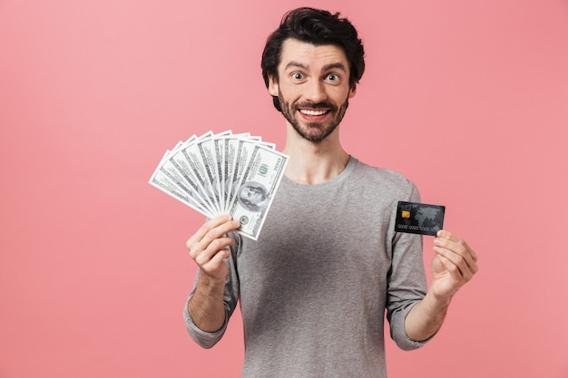 Handsome young bearded brunette man wearing sweater standing over pink, showing credit card, holding money banknotes