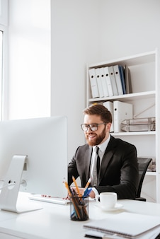 Handsome young bearded businessman using computer.