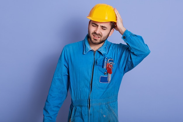 Handsome young bearded caucasian mechanic wearing blue work clothes and yellow hard hat, stands touching his head