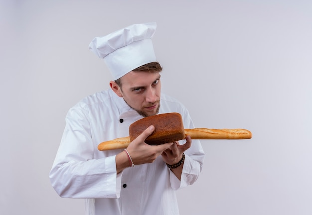 A handsome young bearded chef man wearing white cooker uniform and hat smelling baguette bread with loaf bread while looking on a white wall