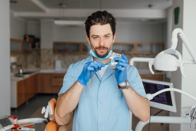 白衣を着たハンサムな若いひげを生やした歯科医は、彼のオフィスに立っている間、プラスチックのlayotを保持しています。