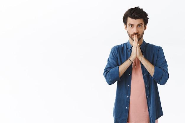 Красивый молодой бородатый парень умоляет о разрешении или одолжении, просит помощи, как сцепить руки у губ и искренне смотреть в камеру, обещая или чего-то желая, стоять у белой стены