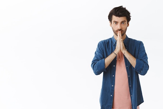 Handsome young bearded guy begging for permission or favor, asking help as clasp hands together near lips and look sincere camera, making promise or want something, stand white wall