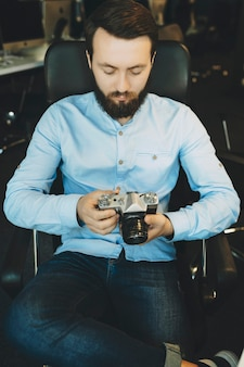 Handsome young bearded male in blue shirt and jeans sitting comfortably on chair with crossed legs and looking attentively at camera in hands with workplace on blurred background