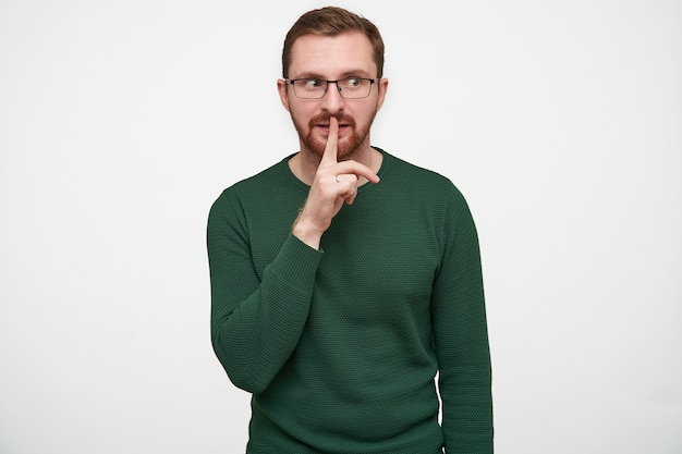 Handsome young bearded male in glasses with brown short hair holding forefinger on his lips and looking aside, asking to keep secret, isolated