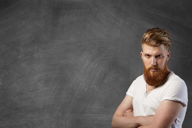 Bel giovane uomo barbuto vestito con una maglietta bianca con maniche arrotolate con espressione seria e sicura, tenendo le braccia incrociate, in piedi contro la lavagna vuota
