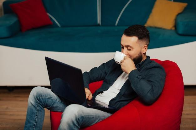 집에서 노트북으로 휴식하는 동안 커피를 마시는 잘 생긴 젊은 수염 남자. 그는 빨간 안락 의자에 앉아 거실에서 커피를 마시고있다.