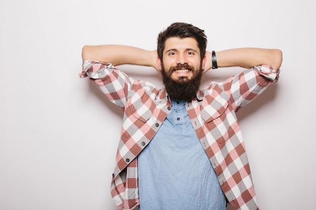 Bel giovane uomo barbuto mano sopra la testa sta guardando la fotocamera mentre in piedi contro il muro grigio