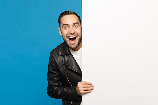 Handsome young bearded man hold big white empty blank billboard for promotional content isolated on blue wall background studio portrait. people sincere emotions lifestyle concept. mock up copy space. Free Photo