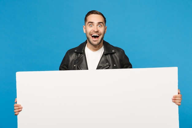 Handsome young bearded man hold big white empty blank billboard for promotional content isolated on blue wall background studio portrait. people sincere emotions lifestyle concept. mock up copy space.