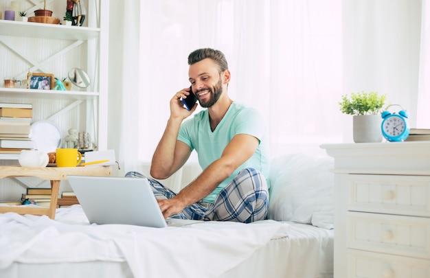 カジュアルな服を着たハンサムな若いひげを生やした男は、ベッドに座って自宅で働いています。ノートパソコンとスマートフォンを持っている自信のある男は、寝室でコーヒーを飲みます。