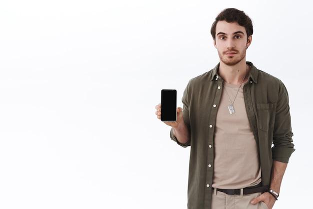Красивый молодой бородатый мужчина в стильном наряде, показывая приложение, мобильную игру или приложение