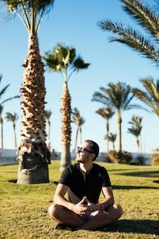 Красивый молодой бородатый мужчина в солнцезащитных очках сидит на траве под пальмами на роскошном курорте летних каникул