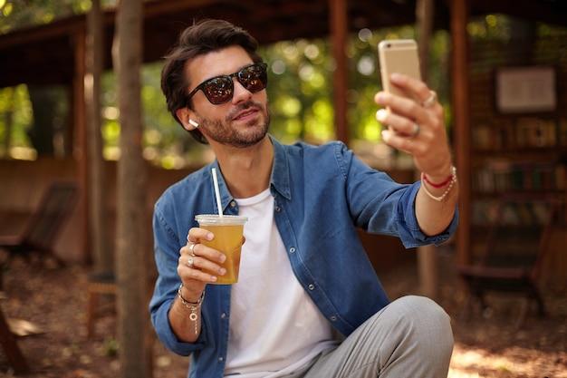 サングラスをかけたハンサムな若いひげを生やした男がジュースを飲みながら公共の庭に座って、スマートフォンで自分撮りをし、カジュアルな服を着て