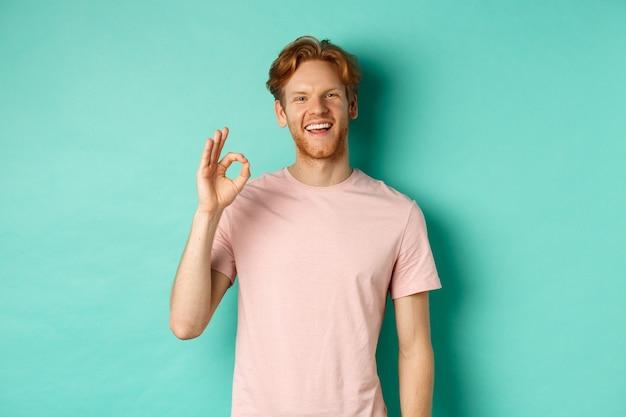 잘 생긴 젊은 수염 난된 남자 t- 셔츠 표시 확인 서명, 하얀 치아와 웃 고 예, 청록색 배경 위에 서 서 당신과 동의합니다.