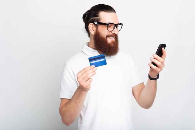 스마트폰과 신용 카드를 사용하여 흰색 티셔츠에 잘생긴 젊은 수염 남자