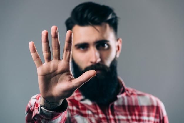 Bel giovane uomo barbuto sta tenendo la mano sulla barba e guarda lontano, su un muro grigio