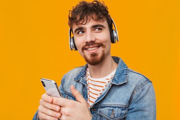 고립 된 헤드폰으로 음악을 듣고 잘 생긴 젊은 수염 된 남자