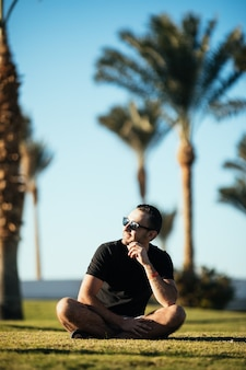 Bel giovane uomo barbuto che osserva da parte in occhiali da sole seduto sull'erba sotto le palme in vacanza estiva.