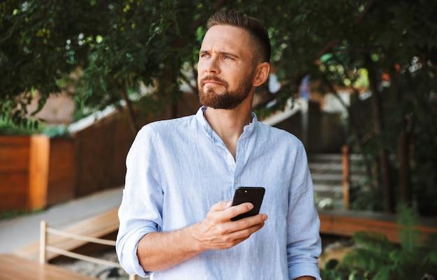 携帯電話を使用して屋外でハンサムな若いひげを生やした男。