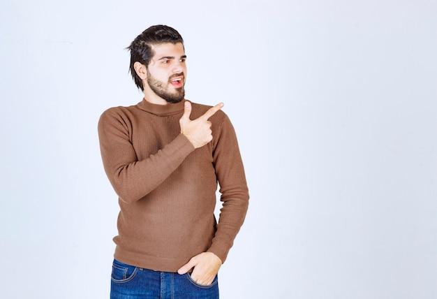 灰色の白い背景を指しているハンサムな若いひげを生やした男。高品質の写真