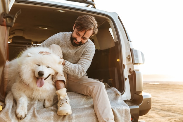 Handsome young bearded man sitting in the back of his car, playing with dog at the beach