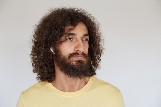 Bel giovane uomo barbuto con capelli ricci castani che osserva da parte pensieroso mentre si ascolta l'allenamento con gli auricolari, vestito con abiti casual mentre posa su sfondo bianco