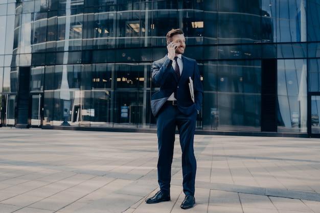 Красивый молодой бородатый офисный работник в темно-синем официальном костюме говорит по мобильному телефону, стоя на улице рядом с бизнес-центром, ожидая встречи партнеров. концепция деловых людей