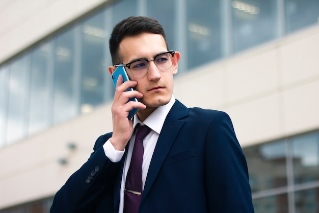 Handsome young beautiful businessman in suit with tie, in glasses talking on cell phone.