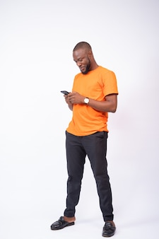 Handsome young black man using his smartphone, texting and chatting online concept on social media, browsing