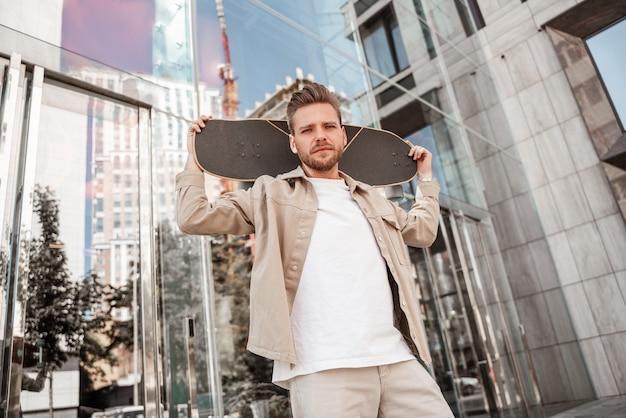 ガラスの建物の間に立っている街の通りで肩にスケートボードを保持しているハンサムな若い金髪の真面目な男。デニムの服を着ています。外で極端なトリックを考えているスポーティでスタイリッシュなスケートボーダー。