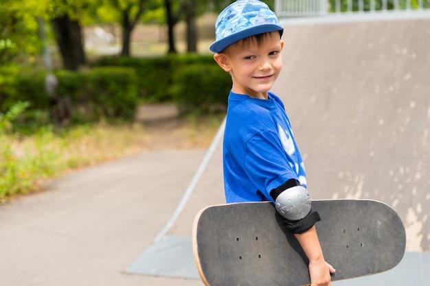 スケートボードを腕に抱えてスケートパークのスロープに近づき、カメラに向かって微笑むハンサムな少年