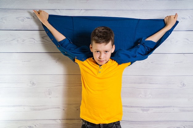 Handsome young boy posing at camera with hands and jacket up at his back