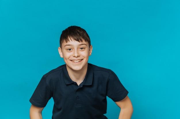 진한 파란색 티셔츠, 넓은 미소를 입고 갈색 눈을 가진 잘 생긴 젊은 소년, 복사 공간이 파란색 배경 위에 흥분 보인다. 청소년 및 교육 개념.