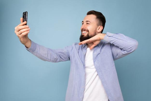 スマートフォンを保持している青い壁の上に孤立して立っているカジュアルなスタイリッシュな服を着ているハンサムな若い黒髪のひげを生やした男
