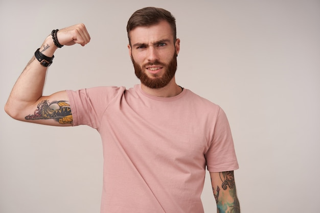 Handsome young brunette man with beard and tattooes raising hand and showing his power, with pleased face and squinting, posing on white in casual clothes