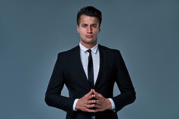 잘생긴 젊은 갈색 머리 모델, 검은색과 흰색 양복을 입고 회색 배경에 고립 된 스튜디오에서 포즈. 비즈니스 남자 초상화입니다. 공간을 복사합니다. 수평 보기입니다.