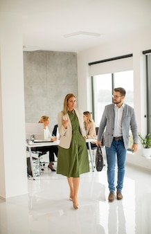 Handsome young business couple walking together at office space