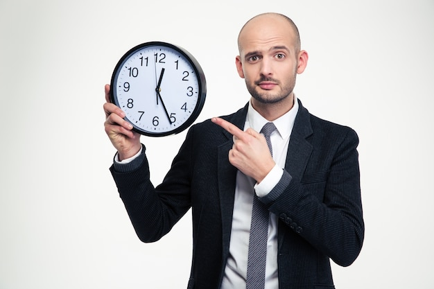 Handsome young business man in black suit and tie pointing on clock over white wall