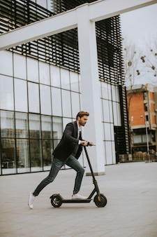 Handsome young business man in a casual clothes riding an electric scooter by an office building on a business meeting