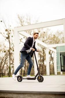 ビジネス会議でオフィスビルのそばで電動スクーターに乗ってカジュアルな服を着たハンサムな若いビジネスマン