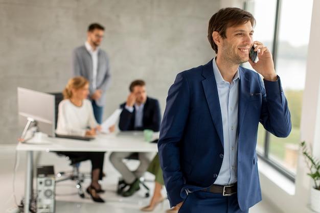 彼のチームの前のオフィスに自信を持って立って、携帯電話を使用してハンサムな若いビジネスマン