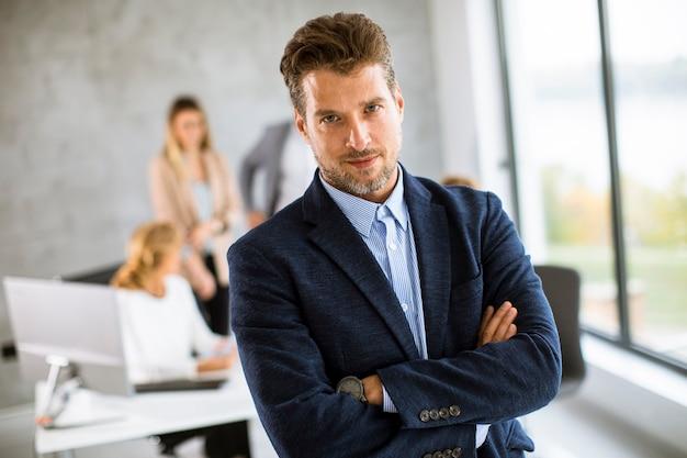 그의 팀 앞에 사무실에 자신감을 서 잘 생긴 젊은 비즈니스 남자